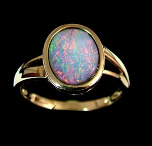 Crystal opal set in yellow gold ring featuring pink and green