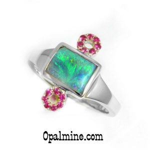 Genuine opal ring featuring a rectangular green blue solid boulder opal with two circles of rubies in sterling silver