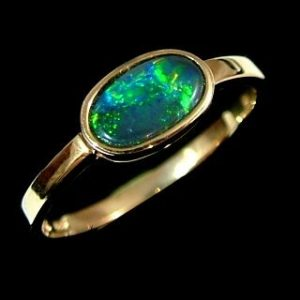 black opal ring featuring green opal